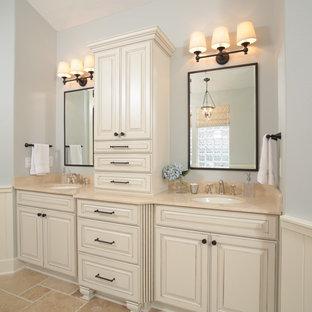Modelo de cuarto de baño principal, tradicional, grande, con armarios con paneles con relieve, puertas de armario amarillas, paredes azules, suelo de piedra caliza, lavabo bajoencimera, encimera de mármol y encimeras beige