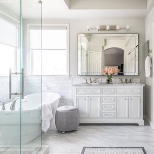 Mid-sized transitional master white tile and marble tile marble floor and white floor freestanding bathtub photo in Sacramento with shaker cabinets, white cabinets, gray walls, an undermount sink, marble countertops, a hinged shower door and white countertops