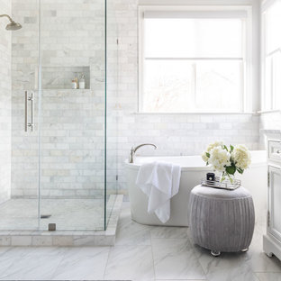 Inspiration for a mid-sized transitional master white tile and marble tile marble floor and white floor freestanding bathtub remodel in Sacramento with shaker cabinets, white cabinets, gray walls, an undermount sink, marble countertops, a hinged shower door and white countertops