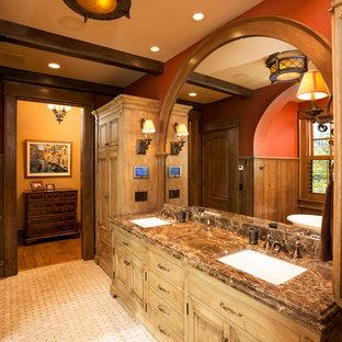 ミネアポリスの大きいトラディショナルスタイルのおしゃれなマスターバスルーム (アンダーカウンター洗面器、中間色木目調キャビネット、ベージュのタイル、赤い壁、御影石の洗面台、落し込みパネル扉のキャビネット、置き型浴槽) の写真