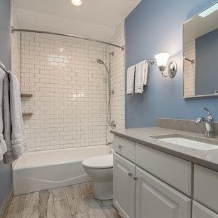 Foto de cuarto de baño principal, clásico renovado, de tamaño medio, con armarios con paneles lisos, bañera esquinera, combinación de ducha y bañera, sanitario de pared, baldosas y/o azulejos blancos, baldosas y/o azulejos de vidrio, paredes azules, suelo de linóleo, lavabo encastrado, encimera de cuarcita y ducha abierta