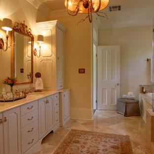 ニューオリンズの中サイズのトラディショナルスタイルのおしゃれなマスターバスルーム (レイズドパネル扉のキャビネット、白いキャビネット、ドロップイン型浴槽、アルコーブ型シャワー、一体型トイレ、ベージュのタイル、茶色いタイル、磁器タイル、ベージュの壁、トラバーチンの床、アンダーカウンター洗面器、大理石の洗面台、ベージュの床、開き戸のシャワー) の写真