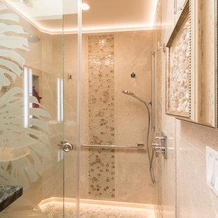 ハワイのトロピカルスタイルのおしゃれな子供用バスルーム (フラットパネル扉のキャビネット、中間色木目調キャビネット、段差なし、壁掛け式トイレ、ベージュのタイル、ライムストーンタイル、ベージュの壁、ライムストーンの床、珪岩の洗面台、ベージュの床、引戸のシャワー、青い洗面カウンター) の写真