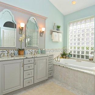Foto de cuarto de baño principal, clásico, de tamaño medio, con puertas de armario grises, jacuzzi, baldosas y/o azulejos beige, baldosas y/o azulejos de porcelana, paredes azules, suelo de baldosas de porcelana, lavabo bajoencimera, encimera de granito, ducha esquinera, armarios con paneles con relieve, suelo beige, ducha con puerta con bisagras y encimeras grises