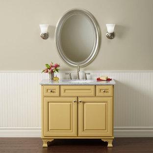 Esempio di una piccola stanza da bagno con doccia classica con ante gialle, pareti beige, parquet scuro, lavabo sottopiano, ante con bugna sagomata, top in marmo e pavimento marrone