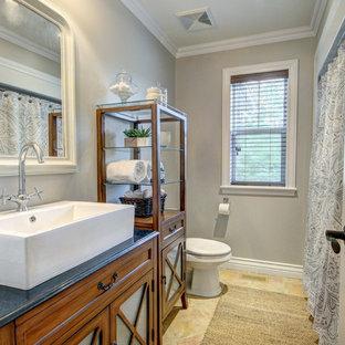 Ispirazione per una stanza da bagno con doccia country di medie dimensioni con ante di vetro, ante in legno bruno, doccia alcova, pareti grigie, pavimento in travertino, lavabo a bacinella, top in quarzo composito, pavimento beige e doccia con tenda
