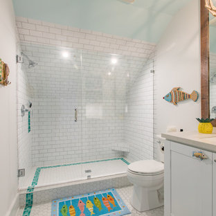 World-inspired shower room in Miami with shaker cabinets, white cabinets, an alcove shower, a two-piece toilet, white tiles, metro tiles, white walls, mosaic tile flooring, a submerged sink, white floors and a sliding door.