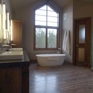 Ejemplo de cuarto de baño principal, contemporáneo, grande, con bañera exenta, ducha empotrada, paredes grises, suelo de corcho, lavabo encastrado, encimera de cemento, suelo marrón y ducha con puerta con bisagras