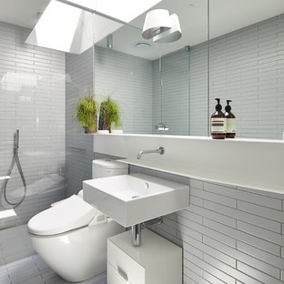 Photo of a contemporary bathroom in Melbourne with flat-panel cabinets, white cabinets, an alcove shower, a two-piece toilet, white tile and a wall-mount sink.