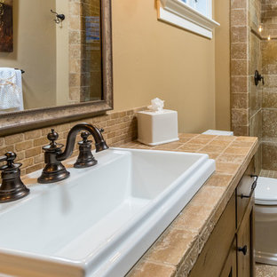 Large mediterranean ensuite bathroom in Other with raised-panel cabinets, beige cabinets, brown tiles, limestone tiles, beige walls, limestone flooring, a built-in sink and brown floors.