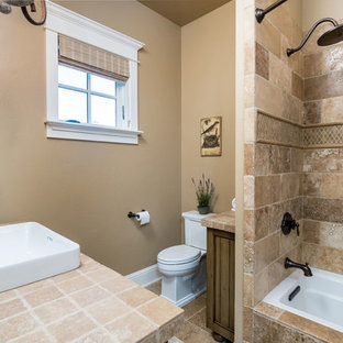 This is an example of a large mediterranean ensuite bathroom in Other with raised-panel cabinets, beige cabinets, brown tiles, limestone tiles, beige walls, limestone flooring, a built-in sink and brown floors.