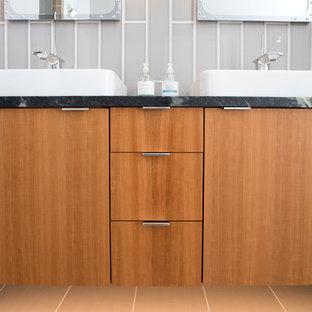 ニューヨークの大きいコンテンポラリースタイルのおしゃれなマスターバスルーム (フラットパネル扉のキャビネット、中間色木目調キャビネット、洗い場付きシャワー、分離型トイレ、グレーのタイル、磁器タイル、グレーの壁、磁器タイルの床、ベッセル式洗面器、ソープストーンの洗面台、グレーの床、開き戸のシャワー) の写真