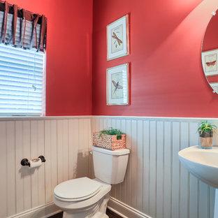 Kleines Klassisches Duschbad mit Sockelwaschbecken, Wandtoilette mit Spülkasten, roter Wandfarbe und dunklem Holzboden in Sonstige