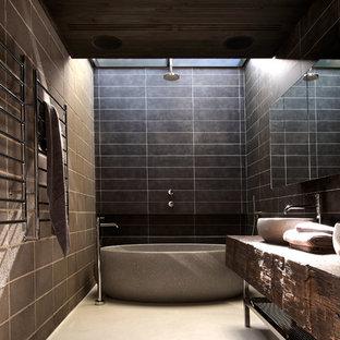 Idee per una stanza da bagno padronale contemporanea di medie dimensioni con lavabo a bacinella, nessun'anta, ante in legno scuro, top in legno, vasca freestanding, piastrelle grigie, piastrelle di cemento e pareti grigie
