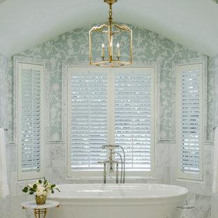 Cette photo montre une salle de bain chic avec une baignoire indépendante, un carrelage blanc, un mur bleu et un sol blanc.