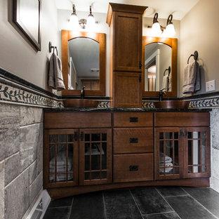 Idée de décoration pour une grande salle d'eau tradition avec un placard à porte shaker, des portes de placard en bois brun, une baignoire en alcôve, un combiné douche/baignoire, un WC séparé, un carrelage gris, du carrelage en ardoise, un mur beige, un sol en ardoise, une vasque et un plan de toilette en granite.