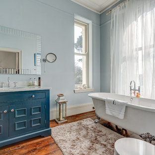 Large transitional dark wood floor claw-foot bathtub photo in Devon with an integrated sink, furniture-like cabinets, blue cabinets, granite countertops and blue walls