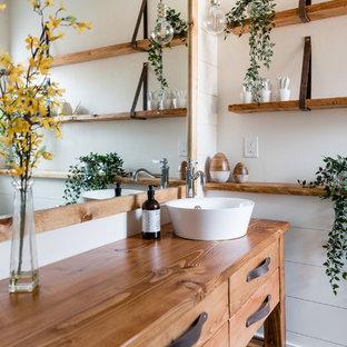 Kleines Landhaus Badezimmer En Suite mit verzierten Schränken, hellbraunen Holzschränken, Eckdusche, Toilette mit Aufsatzspülkasten, weißen Fliesen, Spiegelfliesen, weißer Wandfarbe, Mosaik-Bodenfliesen, Aufsatzwaschbecken, Waschtisch aus Holz und Falttür-Duschabtrennung in Sacramento