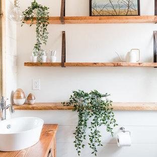 Diseño de cuarto de baño principal, campestre, pequeño, con armarios tipo mueble, puertas de armario de madera oscura, ducha esquinera, sanitario de una pieza, baldosas y/o azulejos blancos, baldosas y/o azulejos con efecto espejo, paredes blancas, suelo con mosaicos de baldosas, lavabo sobreencimera, encimera de madera y ducha con puerta con bisagras