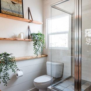 Пример оригинального дизайна: маленькая главная ванная комната в стиле кантри с фасадами островного типа, фасадами цвета дерева среднего тона, угловым душем, унитазом-моноблоком, белой плиткой, зеркальной плиткой, белыми стенами, полом из мозаичной плитки, настольной раковиной, столешницей из дерева и душем с распашными дверями