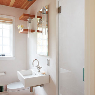 Small trendy 3/4 medium tone wood floor and brown floor alcove shower photo in San Francisco with a wall-mount toilet, white walls, a wall-mount sink and a hinged shower door
