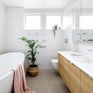 Mid-sized contemporary master bathroom in Melbourne with a freestanding tub, a wall-mount toilet, white tile, ceramic tile, white walls, ceramic floors, an undermount sink, engineered quartz benchtops, white benchtops, flat-panel cabinets, light wood cabinets and beige floor.