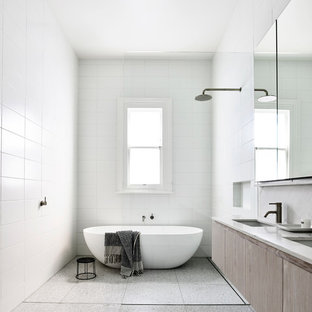 This is an example of a modern master bathroom in Melbourne with flat-panel cabinets, light wood cabinets, a freestanding tub, white tile, an undermount sink, grey floor and white benchtops.