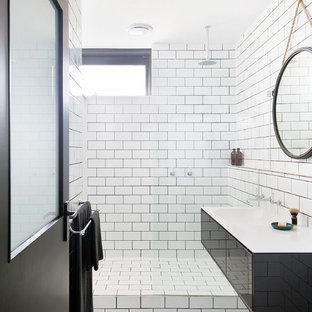 Пример оригинального дизайна: маленькая главная ванная комната в современном стиле с черными фасадами, открытым душем, плиткой кабанчик, белыми стенами, полом из керамической плитки, белой плиткой, подвесной раковиной, столешницей из ламината, плоскими фасадами и открытым душем