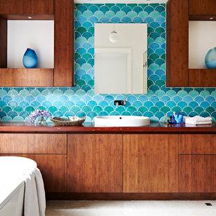 メルボルンのコンテンポラリースタイルのおしゃれなマスターバスルーム (ベッセル式洗面器、フラットパネル扉のキャビネット、中間色木目調キャビネット、木製洗面台、置き型浴槽、青いタイル、青い壁、ブラウンの洗面カウンター) の写真