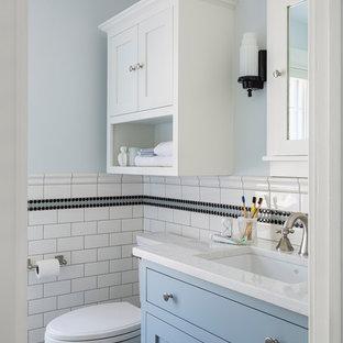 Diseño de cuarto de baño infantil, clásico, pequeño, con armarios tipo mueble, puertas de armario azules, ducha esquinera, sanitario de dos piezas, baldosas y/o azulejos blancas y negros, baldosas y/o azulejos de cerámica, paredes azules, suelo de mármol, lavabo bajoencimera, encimera de cuarzo compacto, suelo gris, ducha con puerta con bisagras y encimeras blancas