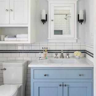 Modelo de cuarto de baño infantil, tradicional, pequeño, con armarios tipo mueble, puertas de armario azules, ducha esquinera, sanitario de dos piezas, baldosas y/o azulejos blancas y negros, baldosas y/o azulejos de cerámica, paredes azules, suelo de mármol, lavabo bajoencimera, encimera de cuarzo compacto, suelo gris, ducha con puerta con bisagras y encimeras blancas