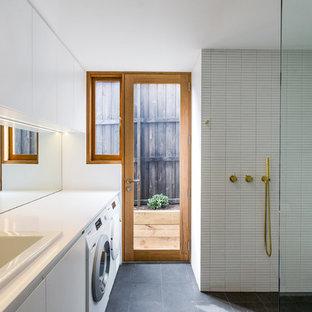 Imagen de cuarto de baño con ducha, contemporáneo, de tamaño medio, sin sin inodoro, con armarios con paneles lisos, puertas de armario blancas, baldosas y/o azulejos blancos, paredes blancas, suelo de cemento, lavabo encastrado, suelo negro, ducha abierta y encimeras blancas