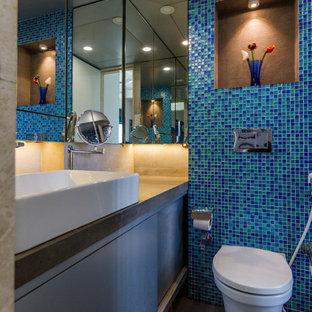 Foto di una stanza da bagno contemporanea con ante lisce, ante grigie, WC sospeso, piastrelle blu, piastrelle verdi, piastrelle di vetro, lavabo a bacinella, pavimento grigio e top grigio