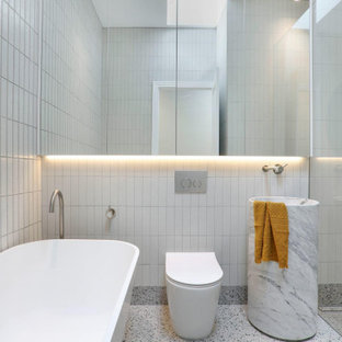 Modern bathroom in Melbourne with a freestanding tub, an alcove shower, a one-piece toilet, white tile, a pedestal sink and grey floor.