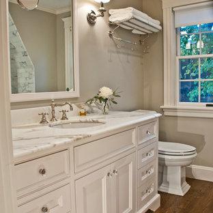 Immagine di una stanza da bagno padronale classica di medie dimensioni con top in marmo, lavabo sottopiano, ante bianche, piastrelle bianche, piastrelle in pietra, pareti beige, parquet scuro e ante con riquadro incassato