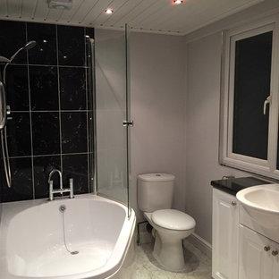 Ejemplo de cuarto de baño principal, actual, pequeño, con puertas de armario blancas, bañera esquinera, combinación de ducha y bañera, sanitario de una pieza, baldosas y/o azulejos negros, baldosas y/o azulejos de porcelana, paredes grises, suelo vinílico, lavabo integrado, encimera de laminado y armarios con paneles lisos