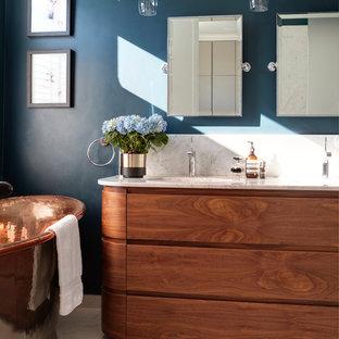 Medium sized contemporary ensuite bathroom in London with a freestanding bath, blue walls, porcelain flooring, marble worktops, white worktops, freestanding cabinets, medium wood cabinets, a submerged sink and beige floors.