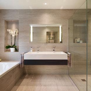 Imagen de cuarto de baño principal, contemporáneo, grande, con armarios con paneles lisos, puertas de armario de madera en tonos medios, ducha empotrada, baldosas y/o azulejos grises, baldosas y/o azulejos de porcelana, paredes grises, suelo de baldosas de porcelana, lavabo de seno grande y bañera encastrada