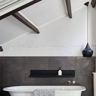 Photo of an industrial master bathroom in Sydney with a claw-foot tub, gray tile, white walls, grey floor, exposed beam and vaulted.
