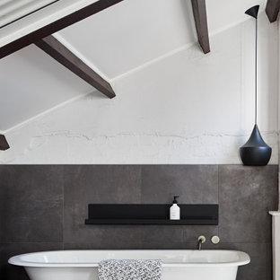 Imagen de cuarto de baño principal y abovedado, urbano, con bañera con patas, baldosas y/o azulejos grises, paredes blancas y suelo gris