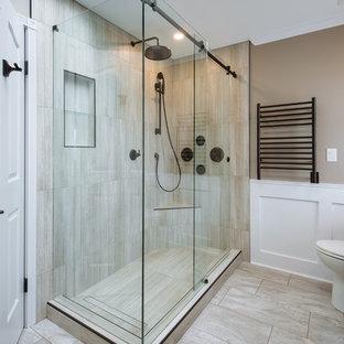 Imagen de cuarto de baño principal, rural, grande, con armarios estilo shaker, puertas de armario de madera en tonos medios, bañera exenta, ducha esquinera, sanitario de dos piezas, baldosas y/o azulejos grises, baldosas y/o azulejos de porcelana, paredes grises, lavabo bajoencimera, encimera de vidrio, suelo gris y ducha con puerta corredera