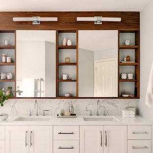 シアトルの中サイズのトランジショナルスタイルのおしゃれなマスターバスルーム (シェーカースタイル扉のキャビネット、白いキャビネット、置き型浴槽、段差なし、白いタイル、大理石タイル、白い壁、磁器タイルの床、アンダーカウンター洗面器、珪岩の洗面台、茶色い床、開き戸のシャワー、白い洗面カウンター) の写真