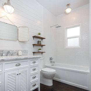 Esempio di una stanza da bagno scandinava di medie dimensioni con ante a persiana, top in marmo, vasca ad alcova, vasca/doccia, WC a due pezzi, piastrelle bianche, piastrelle diamantate, pareti bianche, parquet scuro, ante bianche e lavabo sottopiano