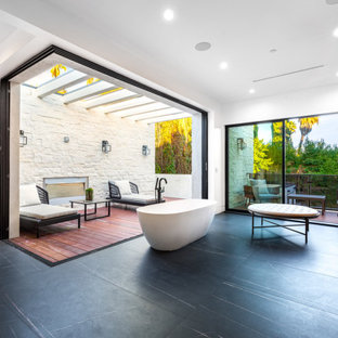 Example of a huge trendy slate floor, black floor and exposed beam freestanding bathtub design in Los Angeles with flat-panel cabinets, dark wood cabinets, white walls, gray countertops and a floating vanity