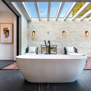 Неиссякаемый источник вдохновения для домашнего уюта: огромная ванная комната в современном стиле с плоскими фасадами, темными деревянными фасадами, отдельно стоящей ванной, белыми стенами, полом из сланца, черным полом, серой столешницей, подвесной тумбой и балками на потолке