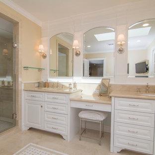 Idée de décoration pour une salle de bain principale tradition de taille moyenne avec un lavabo encastré, un placard avec porte à panneau surélevé, des portes de placard blanches, un plan de toilette en marbre, une douche d'angle, un carrelage beige, un mur jaune, un sol en marbre, une baignoire indépendante, un WC à poser et un carrelage de pierre.