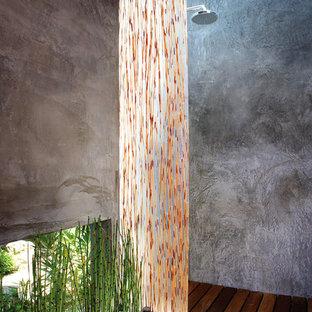 Ejemplo de cuarto de baño de estilo zen, de tamaño medio, con ducha abierta, ducha abierta, armarios con paneles lisos, puertas de armario de madera en tonos medios, paredes grises, suelo de madera en tonos medios, lavabo sobreencimera y encimera de vidrio