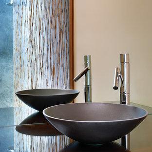 Imagen de cuarto de baño con ducha, asiático, de tamaño medio, con lavabo sobreencimera, armarios con paneles lisos, puertas de armario de madera en tonos medios, ducha abierta, paredes blancas, suelo de pizarra y encimera de vidrio