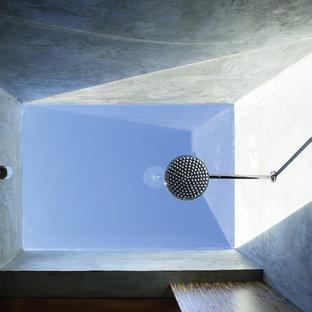 Diseño de cuarto de baño con ducha, asiático, de tamaño medio, con armarios con paneles lisos, puertas de armario de madera oscura, ducha abierta, paredes grises, suelo de pizarra, lavabo sobreencimera y encimera de vidrio