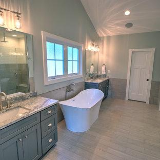 Idee per una stanza da bagno padronale american style con vasca freestanding, zona vasca/doccia separata, WC a due pezzi, piastrelle grigie, piastrelle in ceramica, pavimento con piastrelle in ceramica, lavabo sottopiano, top in granito, pavimento grigio, porta doccia a battente e top grigio